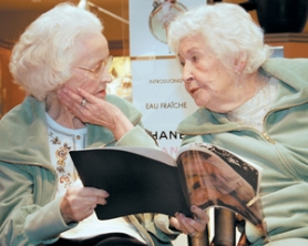 by: Shanda Tice, While looking through a booklet of older photographs of themselves, May Osborn, right, takes a moment to let her best friend Juanita Blair know what special friend she is after the women got makeovers at Saks Fifth Avenue on Tuesday, Feb. 20.