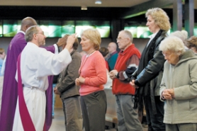 by: Shanda Tice, Parishoners of St. Henry's Catholic Church in Gresham stand in line to receive ashes on Wednesday, Feb. 21. Ash Wednesday is the beginning of Lent.