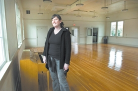 by: John Klicker, Julia Bulfin, executive assistant for the city of Fairview, shows off the sheen of the hardwood floors in the newly renovated community center on Harrison Street. Bulfin has heard stories about where people's desks were when the building was City Hall. The former grange site is available for gatherings.