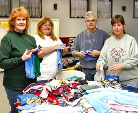 by: David F. Ashton, Tremont Evangelical Church members Vivian O'Day, Pam DuClos, Pastor Ed Kelly, and Margie Bean prepare the clothing they give to the needy each month.