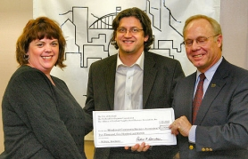 by: David F. Ashton, Jane Glanville, president, and Barry Evans, VP, of the Woodstock Community Business Association, picking up their grant check in January from APNBA president Pat Donaldson.