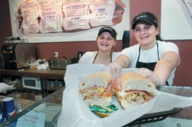 by: John Klicker, Danielle Kent, left, and Jackie Kent, dish up a Chicken Cordon Bleu Sargo's Sub sandwich on Tuesday, Feb. 27. It was the sisters' first week on the job. Sargo's Subs is in the Wood Village Town Center, next to Starbucks.