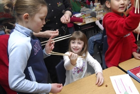 by: Vern Uyetake, Stafford Primary fourth-grader Grace Lamb, left, helps first-grader Caitlin Strader learn to use chopsticks. The event at Stafford was part of a Chinese New Year celebration.