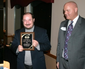 by: Marcus Hathcock, Citizen of the Year Ernie Brache, left, accepts his award from Chamber Banquet Emcee Bill Bailey.