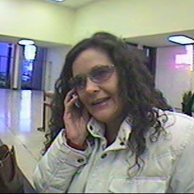 by: Photo provided by WCSO, Detectives with the Washington County Fraud and Identity Theft Enforcement team are asking for the public's help locating a fraud suspect, Jenine Catherine Napoli, 45 years old, pictured here standing at a bank's counter late in 2006.
