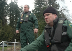 by: patrick sherman, Detective Ken Link (foreground) and Deputy Doug Olsen watch a live video feed from the bottom of the Willamette, hoping to catch site of Kline's car.