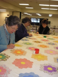 by: ellen spitaleri, Linda Seeley, Gretchen Stelling and Darlene McDonald, all members of The Friends of the Milwaukie Center Quilters, work on hand stitching a quilt in a pattern called grandmother's flower garden.