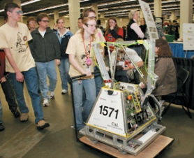 by: Shanda Tice, Center for Advanced Learning senior Tasha Larson is followed by a mix of team members and supporters as she wheels their robot out to compete in the second elimination round of the day at the Robotics Competition on Saturday, March 3, at Memorial Coliseum.