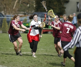 by: Chase Allgood, Pacific's Marissa Gottlob gets checked by Jamie Shumaker of Puget Sound during Sunday's lacrosse game.