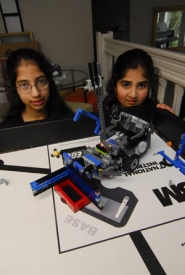 "by: Vern Uyetake, Rohisha Adke, an 8th grader at Waluga Jr. High School, and her sister, Anisha Adke, a 5th grader at Westridge Elementary, show off their creation, a robot they nicknamed ""Kanga."""