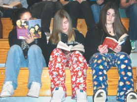 by: Jenifer DeWolfe, Julianna Stai, and Kalie Wilkinson read books Friday, March 16, in the gymnasium during the school's reading marathon. Some students wore pajama pants and slippers to get into the spirit of the event.