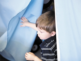 by: Chase Allgood, Toddler Henry Kottke, who is autistic, peers from behind a curtain at West Union Elememtary School.
