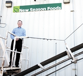 by: CHASE ALLGOOD, Mike Frandsen, CEO and president of New Season Foods in Forest Grove, stands atop some food processing machinery at the company's plant on Yew Street.