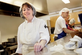 by: Jonathan House, MULTI-FACETED JOB — Loaves & Fishes kitchen coordinator Theresa Thornton not only cooks the meals at the Tigard Senior Center, but she also manages the volunteers who help out each day.