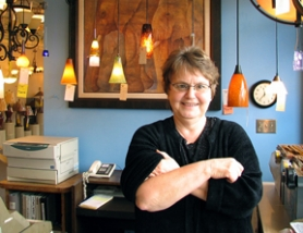 "by: Mikel Kelly, SHE'S IN CHARGE — Julie Mottern, manager of the Beaverton Light Shoppe, at 5355 S.W. Western Ave., greets customers at the entrance to her store. ""We're just little guys,"" she says, ""and we stay under the radar."""