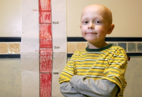 by: Jonathan House, Jack Fried, a second-grader at Cedar Mill Elementary School, stands in front of a fund-raiser thermometer, which shows how much money the school has raised to purchase wagons for Doernbecher Children's Hospital. The wagons will be used to transport children or their luggage.