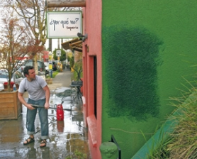 by: JIM CLARK, ¿Por Qué No? taqueria owner Bryan Steelman power-washes his North Mississippi Avenue storefront. The dark paint on the side of the buidling covers graffiti.