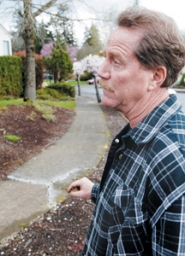 by: Matthew Ginn, Property owner Tom Holland says he is concerned about the inconsistency of code enforcement in Gresham. Here, he shows some cracks marked in front of one of his rental homes on Monday, March 26.
