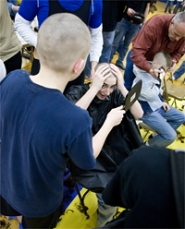 by: Chase Allgood, Banks High School student Trask Bowden checks his clean-shaven head while Spencer Sherrill holds a mirror for him during a show of solidarity last Friday for wrestler Mitch Engeseth, who has been diagnosed with Burkitt's Lymphoma.