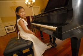 by: Vern Uyetake, Adria Ye sits at the piano in her Lake Oswego home. The Westridge Elementary fourth-grader's favorite composers include Tchaikovsky and Rachmaninoff.