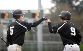 by: JONATHAN HOUSE, KNUCKLES — Tigard's Miles Kreisberg (left) congratulates Andrew Woolfe after he scored in the third inning of the Tigers' game with McNary on Monday. Tigard rallied to score a 6-3 victory.