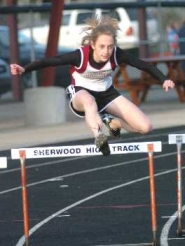 by: DAN BROOD, UP AND OVER — Sherwood freshman Kathryn Mariman clears the hurdle on her way to victory last week. She also won the pole vault competition.