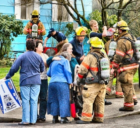 by: David F. Ashton, While firefighters checked on her wellbeing, neighbors gathered to comfort the woman whose home was damaged by a basement fire.