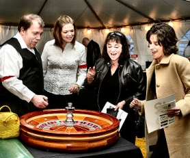 "by: David F. Ashton,  ""Place your bets"" cries roulette croupier Ryan McKenzie, as he spins the ball for high rollers Marilyn McKenzie, Colleen Beckmeyer and Marla Fuller."