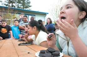by: John Klicker, Monica Manzo, 11, eats oreos competitively at thePolice Activity League on Friday, March 30.