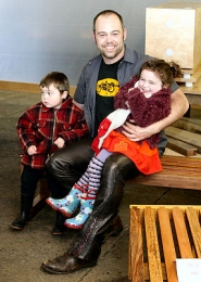 by: David F. Ashton, Charley Wheelock, KaPow Design, sits on one of his handmade benches, with his kids, Madeleine and Leo.