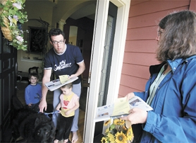 by: Chase Allgood, Volunteer Linda Taylor (right) welcomes Glenn Perrault at the door of his home. With him are his children, Landon and Makenzie, along with their dog Bailey.