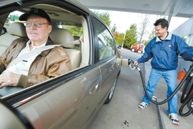 by: Jaime Valdez, FILL 'ER UP — Sami Ghaffari, owner of the Union 76 station at Pacific Highway and Walnut Street, fills up the tank of Gene Dooley, who says he supports an initiative to let voters decide if they want to keep the city's new 3-cents-per-gallon gas tax.