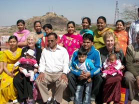 by: BARBARA SHERMAN, A family visiting the Meherangarth Fort in Jodhpur invited Mary Feller of Tigard (front row, second from left) and Barbara Sherman (front row, far right) to hold their babies and pose for photos.