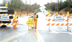 "by: File photo, In this photo from December 2005, Washington County employee Herbert Bridges installs ""road closed"" signs next to Deerfield Drive because of high water that had covered the road. The county plans to make improvements to the roadway from the road barriers in the foreground to those in the background."