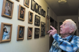 by: Shanda Tice, Ralph Clinton points to pictures along the wall of his house in Pleasant Valley. Clinton, who died at age 87 Tuesday, worked his family's century farm.