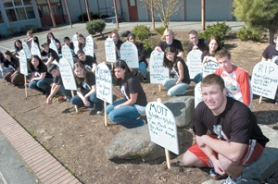 by: John Klicker, Students place themselves behind mock tombstones after being chosen to represent the number of people killed by drunken drivers during the 'Every 15 Minutes' program.