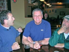 by: Chad Abraham, Chuck Fagan, center, smiles as George Farrell argues a point at Main Street Ale. The brewpub's regulars are planning a charity fishing trip later this month to