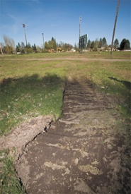 by: Chase Allgood, Tractor tires have already disturbed some of the ground at Forest Grove's Lincoln Park near the spot where a murder took place in May 2004. Videotape, shot by police from helicopters will help to preserve the crime scene for court records.