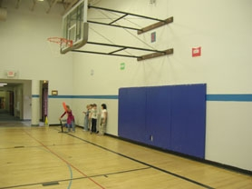 by: Cori Bolger, Hallinan Elementary School students play in gym class near padding on the wall of the school basketball court. A lawsuit against the school district charging a teenager was injured against the formerly pad-less wall in a basketball game two years ago is due to go to trial May 15.