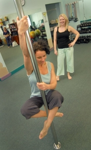 by: Vern Uyetake, Pole dancing instructor Kelly Klingele, right, watches as Kathy Evans learns a pole dance movement.