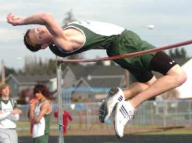 by: DAN BROOD, UP, UP AND AWAY – Tigard High School junior Spencer Patterson soars over the crossbar in the high jump competition during last week's dual meet at Forest Grove.