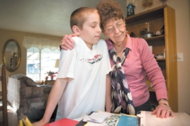 by: John Klicker, Connie McClendon shares a hug with her 10-year-old grandson Jacob as they look through their scrapbook at pictures of Jacob with his father, Jeff, who died in 2003.
