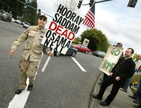 "by: Jaime Valdez, Michael from the Portland area walks through a crosswalk on S.W. Hall Boulevard in front of protesters shouting, ""Hooray, Sadam is dead."" Protesters and counter-protesters showed their support on a sidewalk near the Embassy Suites Hotel where political adviser Karl Rove spoke to Washington County Republicans Friday."
