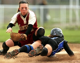 by: Tommy Whitcomb, Forest Grove shortstop Katy Brosig tries to lay a tag on a Newberg baserunner during Friday's softball game.