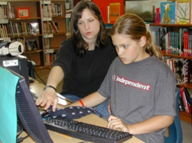 by: Jim Hart, Cedaroak Park Primary School Teacher-Librarian Tara Pittius, left, shows fifth-grader Mariah Gatti how to store digital information that the youth found while researching a science