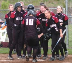 by: DAN BROOD, A HERO'S WELCOME — Tualatin senior Natalie Taylor (10) is greeted at home plate by her Timberwolf teammates after she hit a sixth-inning home run. The homer completed the cycle for Taylor.