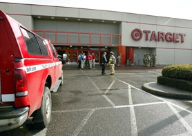 by: Jaime Valdez, READY FOR THE CLEAN-UP – Tualatin Valley Fire & Rescue firefighters stand outside the Target store at 9009 S.W. Hall Blvd. on Thursday afternoon after evacuating employees and customers.