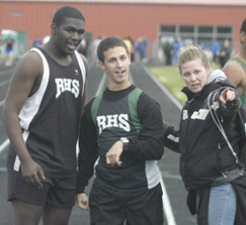 by: David Ball, Reynolds senior Blake Shelly, center, is met at the finish line by teammate Chris Benjamin and sprints coach Anna Gray after completing the 100-meter dash during a dual-meet against Gresham last week.