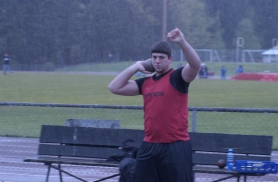 by: Michael Cade, Sandy's Michael T. Lynch endures the rain, sleet and hail during his shot put throw.