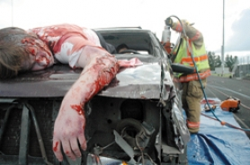 "by: david stroup, Senior Jeremy Weidman lies ""dead"" on the hood of one of the cars as a CCFD #1 firefighter dismantles the vehicle to rescue the people inside in a realistic enactment of the response to a crash."